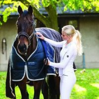Blonde woman attaching an outer rug to a horse wearing the Horsewear Vari-Layer Liner