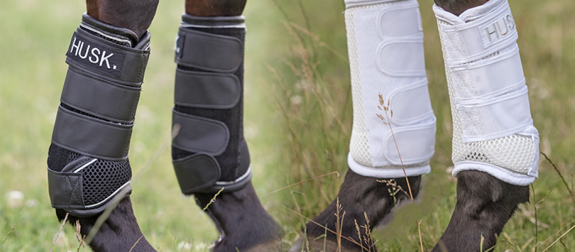 A pair of black and a pair of white protective horse boots by The Husk